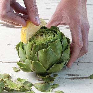 rubbing lemon on cut fresh artichokes