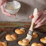 brushing baked rolls with butter
