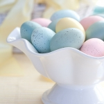 a white bowl holding speckled Easter eggs