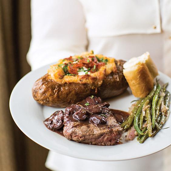 Paula Deen holding a plated steak dinner